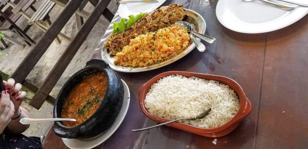 À gauche : Pirao, soupe épaisse faite à base de morceaux de poissons et de farine de manioc, un légume racine.En arrière: Farine de manioc avec des épices et de petites crevettesÀ droite: riz blanc